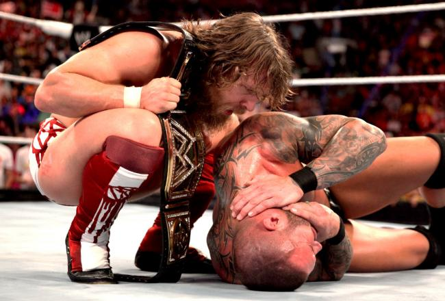 Daniel Bryan (left) stands over a fallen Randy Orton