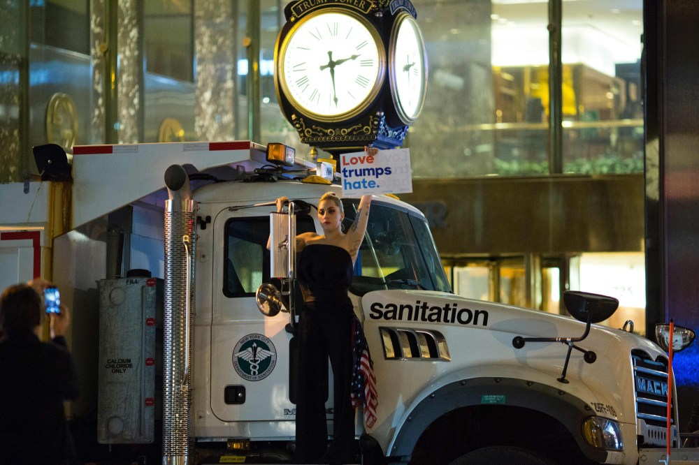 TOPSHOT - Musician Lady Gaga stages a protest against Republican presidential nominee Donald Trump on a sanitation truck outside Trump Tower in New York City after midnight on election day November 9, 2016. Donald Trump stunned America and the world, riding a wave of populist resentment to defeat Hillary Clinton in the race to become the 45th president of the United States. The Republican mogul defeated his Democratic rival, plunging global markets into turmoil and casting the long-standing global political order, which hinges on Washington's leadership, into doubt.  / AFP / DOMINICK REUTER        (Photo credit should read DOMINICK REUTER/AFP/Getty Images)